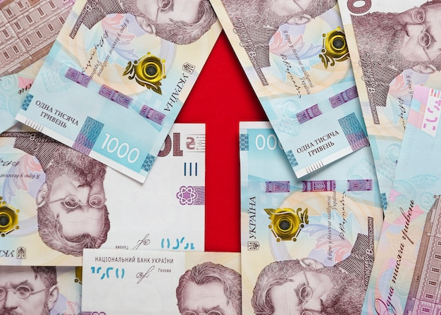 Ein pfeil mit banknoten von ukrainischen griwna und euro