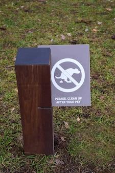 Ein pfosten im park mit einem schild, das hundebesitzer auffordert, die exkremente nach ihren haustieren zu beseitigen
