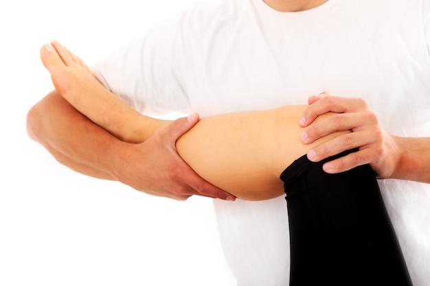 Ein physiotherapeut, der versucht, das bein auf weißem hintergrund zu reparieren