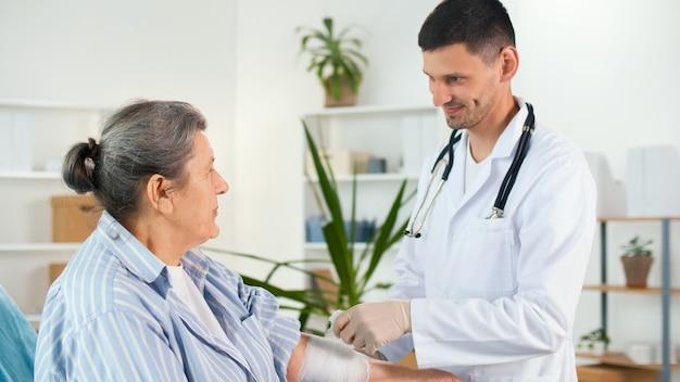 Ein physiotherapeut legt im büro der klinik einen verband am verletzten arm eines patienten an. medizinische verfahren in der klinik. konzept des medizinischen dienstes der krankenversicherung.