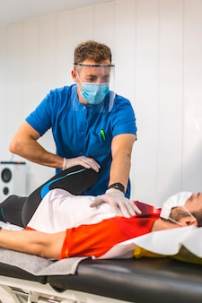 Ein physiotherapeut mit maske und bildschirm, der einem patienten eine beinmassage gibt. physiotherapie mit schutzmaßnahmen gegen die coronavirus-pandemie. osteopathie, therapeutische chiromassage