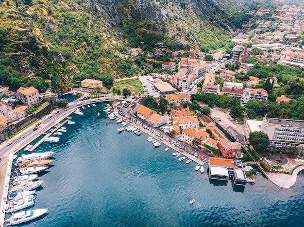 Ein pier mit yachten vor dem hintergrund der hohen berge festgemacht, luftaufnahme. sonniger tag. kotor, montenegro.