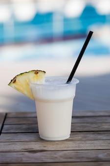Ein pina colada-cocktail vor der kulisse eines blauen außenpools