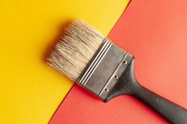 Ein pinsel am gelben und roten papierhintergrund