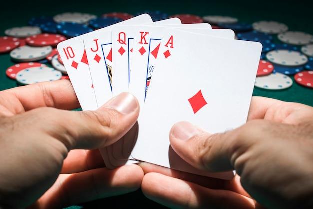 Ein pokerspieler, der royal flush karten hält