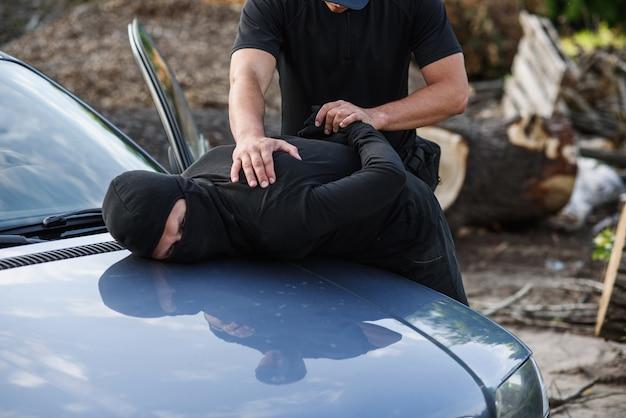 Ein polizist verhaftete den täter in einer maske mit einem gestohlenen auto und legte ihm handschellen an die motorhaube.