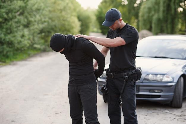 Ein polizist verhaftete einen täter mit dem gestohlenen auto und legte ihm handschellen an.