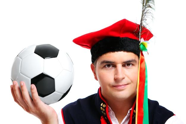 Ein polnischer mann in tracht mit fußball