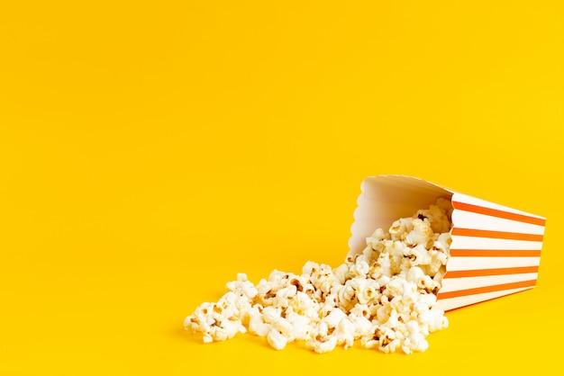 Ein popcorn der vorderansicht innerhalb der packung gesalzen frisch isoliert auf gelb