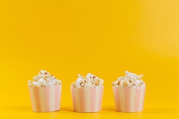 Ein popcorn der vorderansicht innerhalb der pakete, die auf gelbem schreibtisch isoliert werden
