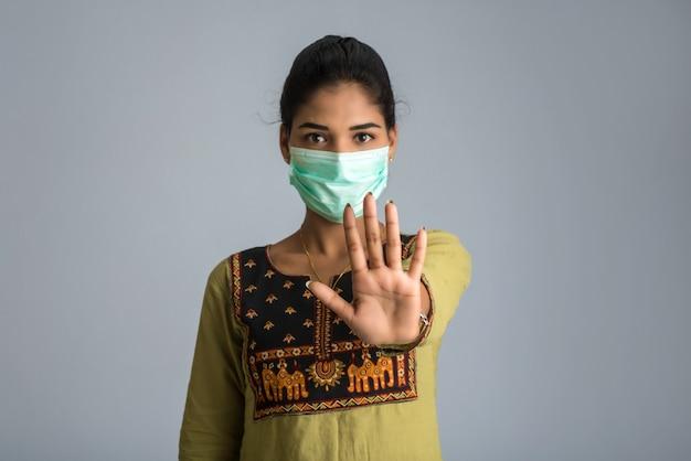Ein porträt der frau mit der medizinischen gesichtsmaske, die stoppschild mit händen zeigt. gesundheits- und medizinkonzept