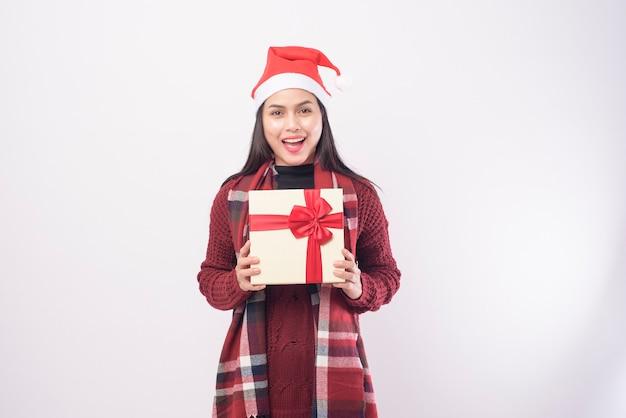 Ein porträt der jungen frau, die roten weihnachtsmannhut trägt