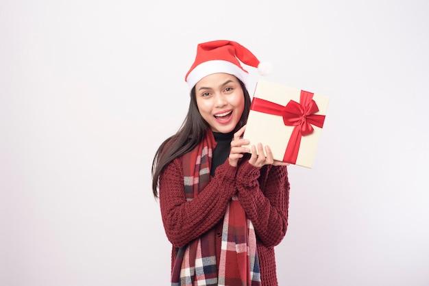 Ein porträt der jungen lächelnden frau, die roten weihnachtsmannhut trägt