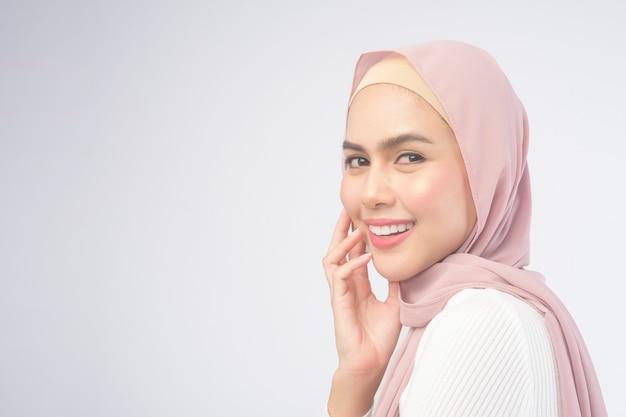Ein porträt der jungen lächelnden muslimischen frau, die einen rosa hijab über weißem hintergrundstudio trägt.