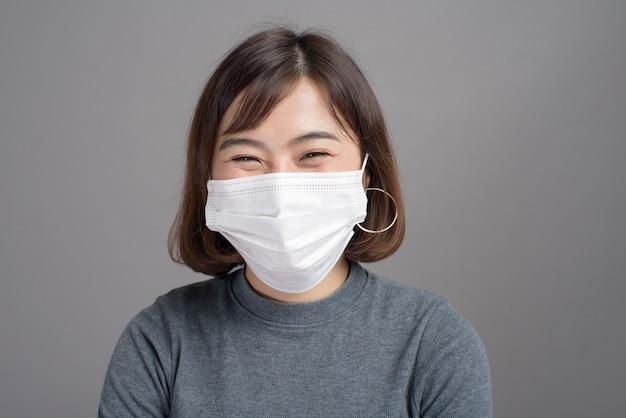 Ein porträt der jungen schönen asiatischen frau, die eine chirurgische maske o trägt