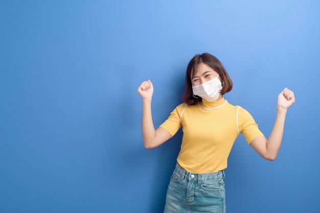 Ein porträt der jungen schönen asiatischen frau, die eine chirurgische maske trägt