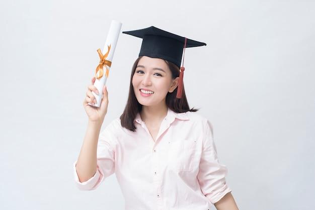 Ein porträt der schönen jungen asiatischen frau mit bildungskappe über weißraumstudio, bildungskonzept.