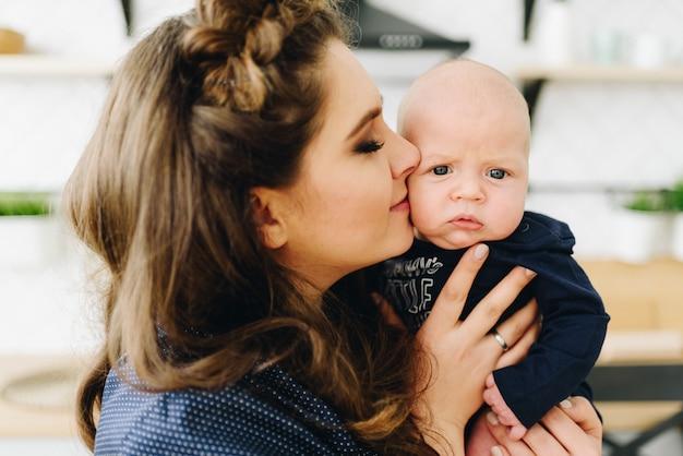 Ein porträt der schönen jungen kaukasischen frau, die ihr baby küsst