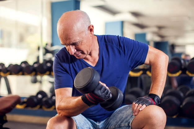 Ein porträt des älteren mannes im sporttraining mit hanteln. menschen-, gesundheits- und lebensstilkonzept