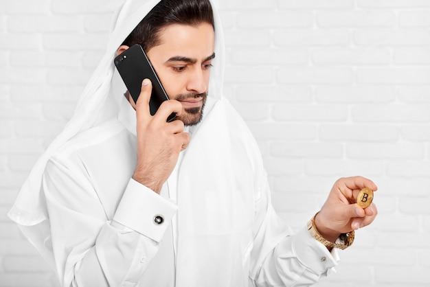 Ein porträt des arabischen mannes, der goldenes bitcoin in einer hand hält und am handy mit einem anderen spricht.