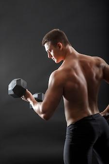 Ein porträt des bodybuilders in den schwarzen eignungskurzen hosen, die mit dummkopf aufwerfen