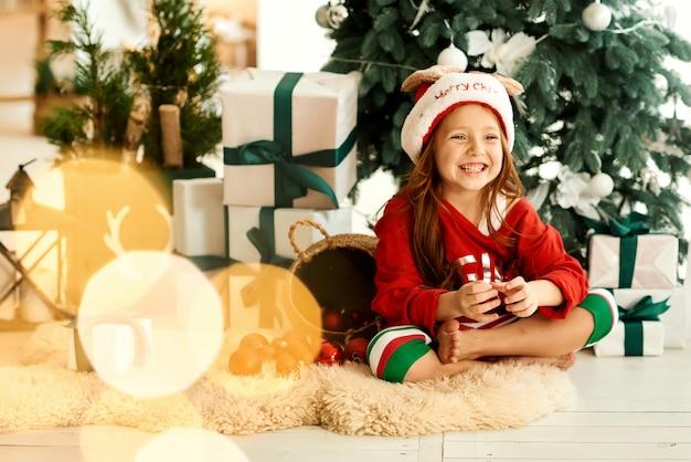 Ein porträt des glücklichen kindes im pyjama in der küche auf dem weihnachtsbaum