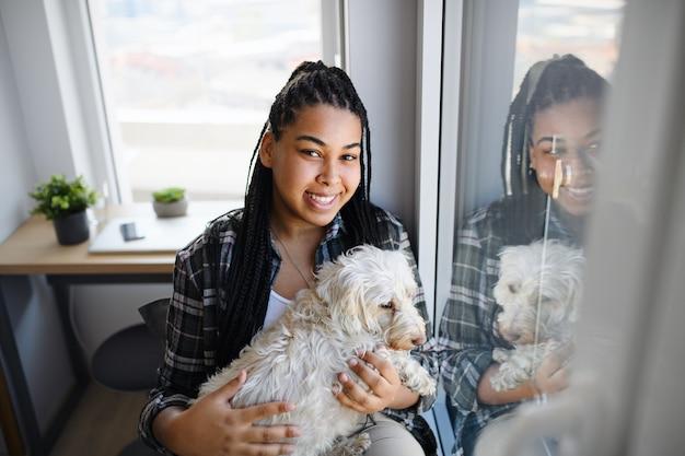 Ein porträt des glücklichen teenager-mädchens mit dem hund, der zuhause zuhause sitzt und kamera betrachtet.