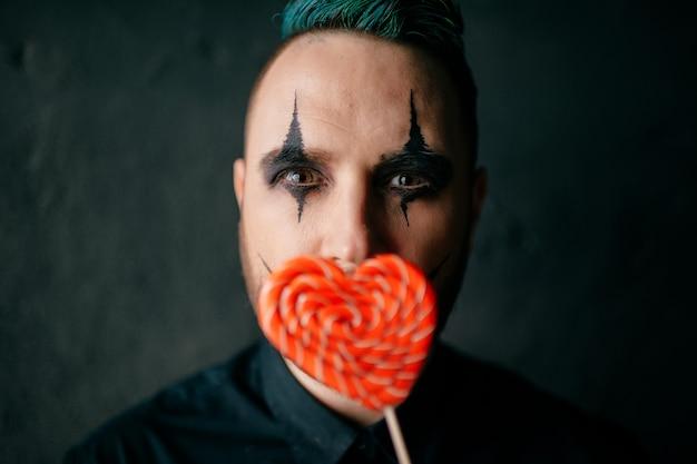 Ein porträt des gotischen schwarzen clowns, der mit lutscher aufwirft