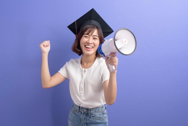 Ein porträt des graduierten asiatischen studenten, der megaphon lokalisiertes purpur hält