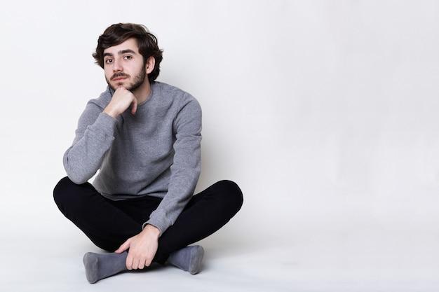 Ein porträt des jungen hipsters mit heller haut und trendigem bart, der auf dem boden sitzt, gekreuzte beine.