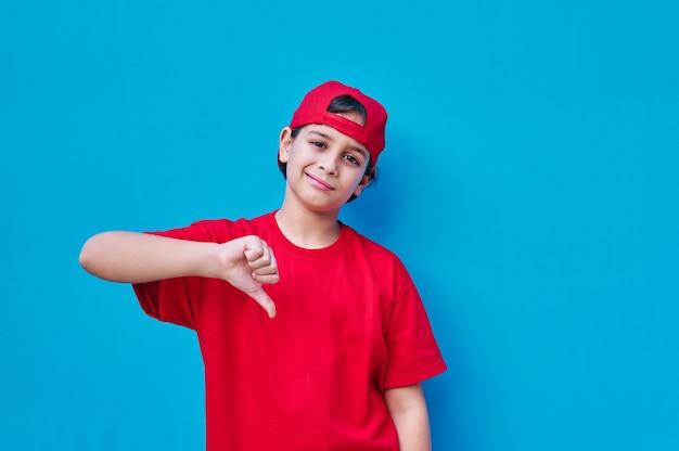 Ein porträt des jungen im t-shirt und in der roten kappe mit daumen nach unten