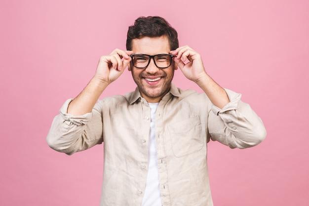 Ein porträt des jungen lächelnden gutaussehenden geschäftsmannes im freizeithemd, das seine brille berührt.