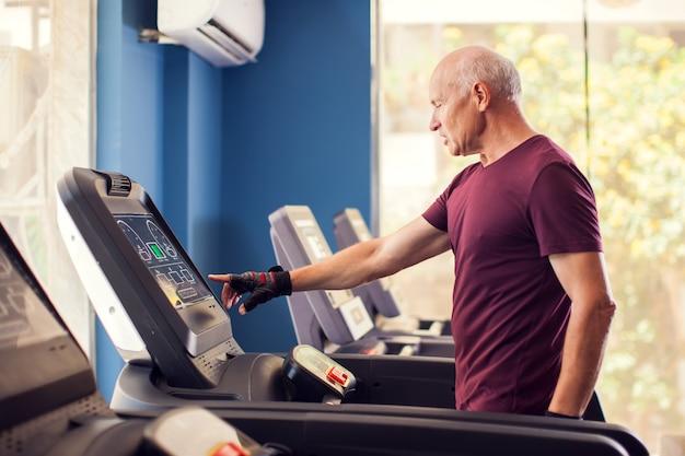 Ein porträt des kahlen älteren mannes im sporttraining in der cardio-zone. menschen-, gesundheits- und lebensstilkonzept