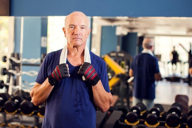 Ein porträt des kahlen älteren mannes in der turnhalle, die kamera betrachtet. menschen-, gesundheits- und lebensstilkonzept
