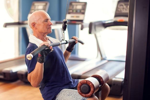 Ein porträt des kahlen älteren mannes in der turnhalle, die rückenmuskeln trainiert. menschen-, gesundheits- und lebensstilkonzept