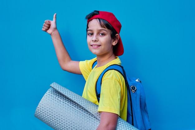 Ein porträt des lächelnden jungen im gelben t-shirt und in der roten kappe mit einer matte und einem rucksack