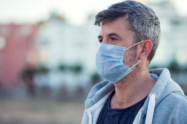 Ein porträt des mannes mit der medizinischen gesichtsmaske im freien. konzept für menschen, gesundheitswesen und medizin