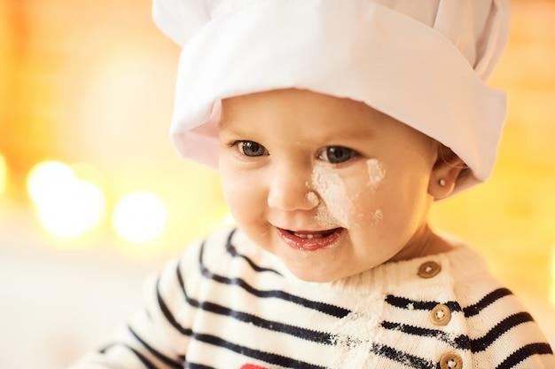 Ein porträt des netten kindes gekocht und mit mehl und teig in der küche gespielt