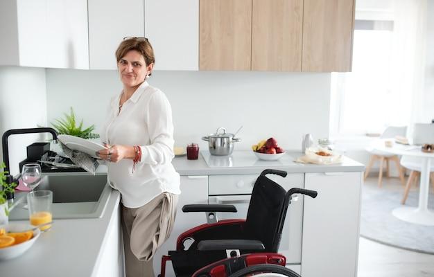 Ein porträt einer behinderten reifen frau im rollstuhl zu hause, die das frühstück zubereitet.