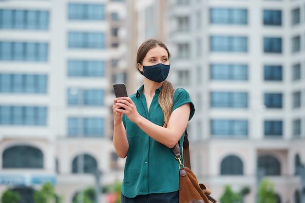 Ein porträt einer frau in einer medizinischen gesichtsmaske hält ein smartphone, während es im zentrum der stadt geht