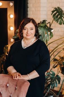 Ein porträt einer geschäftsfrau in einem schwarzen kleid und mit perlen um den hals steht in der nähe eines stuhls im inneren.