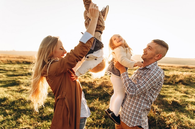 Ein porträt einer glücklichen familie, die im sonnenuntergang spielen