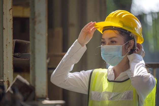 Ein porträt einer industriellen ingenieurin mit maske, die in einer fabrik steht.
