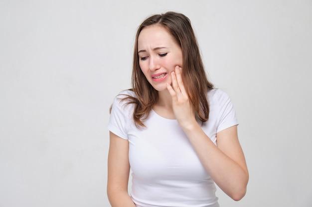 Ein porträt einer jungen frau in einem weißen hemd hält seine hand an seiner wange. das konzept der zahnschmerzen.