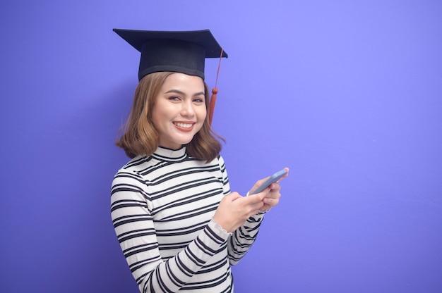 Ein porträt einer jungen frau mit abschluss auf blauem hintergrund