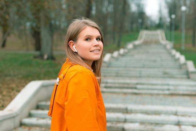 Ein porträt einer netten frau, die die kamera im park betrachtet, bereit, die treppe hinaufzulaufen