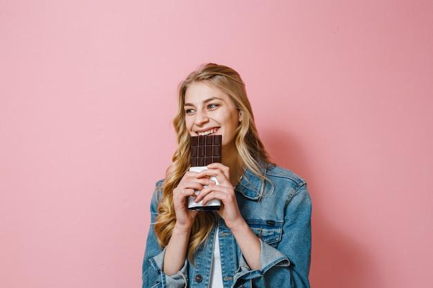 Ein porträt einer schönen blonden frau, die schokolade isst, ist aufgeregt
