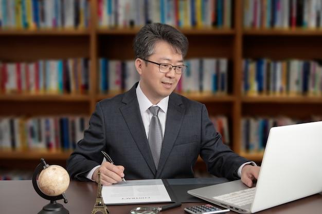 Ein porträt eines asiatischen männlichen geschäftsmannes von mittlerem alter, der an einem schreibtisch sitzt.