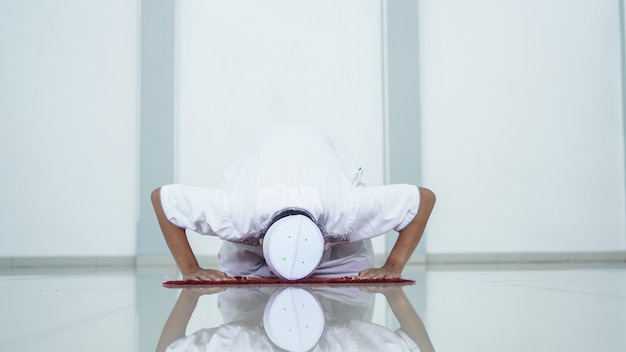 Ein porträt eines asiatischen muslimischen mannes, der in der moschee betet, der gebetsname ist sholat, sujud bewegung auf sholat
