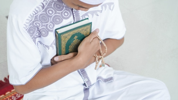 Ein porträt eines asiatischen muslimischen mannes, der koran und tasbih hält